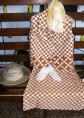 Moda del tempo libero anni 50 / 60 - abito con gonna e giacchino motivi geometrici toni maron e accessori
