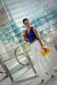 pantalone bianco a zampa e top viola con borsa design Pfister