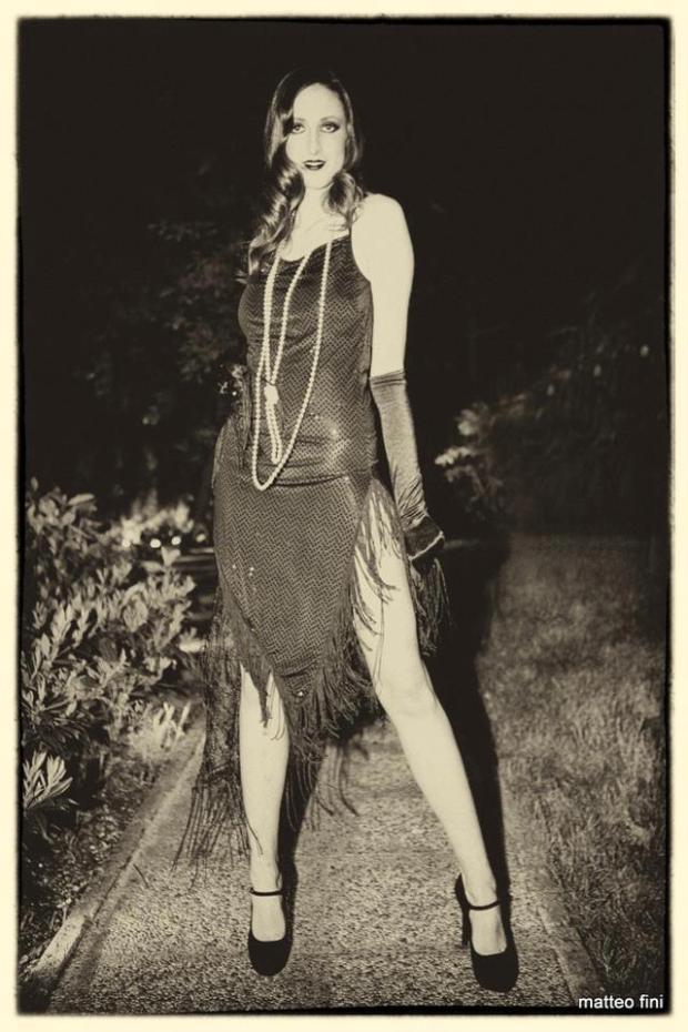 estiti charleston - vestiti flapper - vestiti anni 20 30 - vestito aderente nero con taglio sbieco e frangia abbinato ad accessori in nero - la camelia collezioni